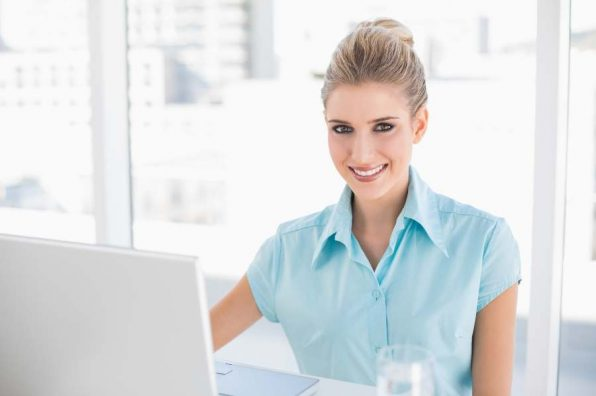 Smiling well dressed businesswoman in bright office using laptop